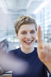 Portrait of blond businesswoman touching at glass pane - PNEF00701