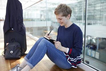 Blond businesswoman sitting on ground, writing in notebook - PNEF00704