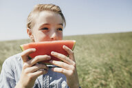 Boy on a field eating a watermelon - KMKF00290