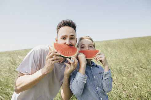 Portrait of young man and boy on a field holding watermelons - KMKF00293