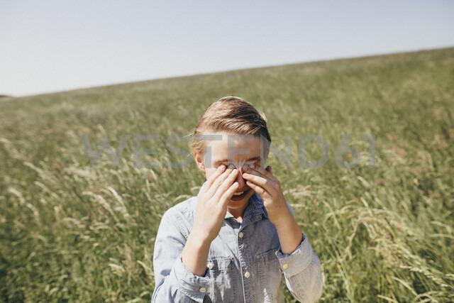 Boy on a field rubbing his eyes - KMKF00296