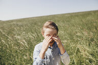 Boy on a field rubbing his eyes - KMKF00296