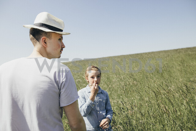 Young man and boy standing on a field - KMKF00299