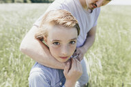 Portrait of boy and young man in a field - KMKF00302