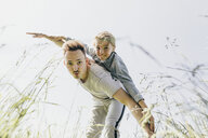 Young man and boy in a field pretending to fly - KMKF00308