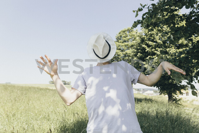 Man covering his face with a hat in field - KMKF00311