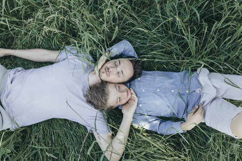 Young man and boy lying in field - KMKF00314