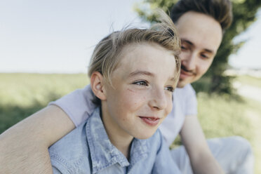 Portrait of young man embracing smiling boy at a field - KMKF00320