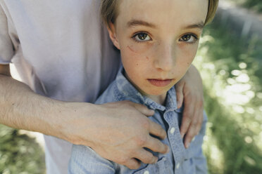 Portrait of boy being embraced by a man - KMKF00323