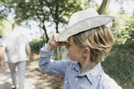 Boy wearing a hat on forest path - KMKF00329