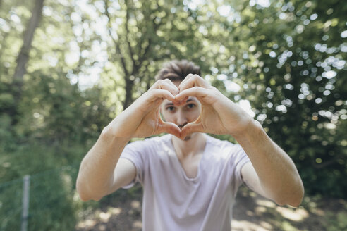 Young man making a heart with his fingers on forest path - KMKF00332