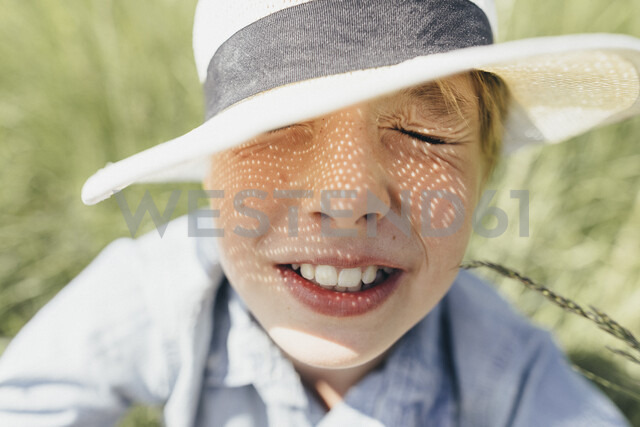 Boy with closed eyes wearing a hat sitting in field - KMKF00341 - Katharina Mikhrin/Westend61