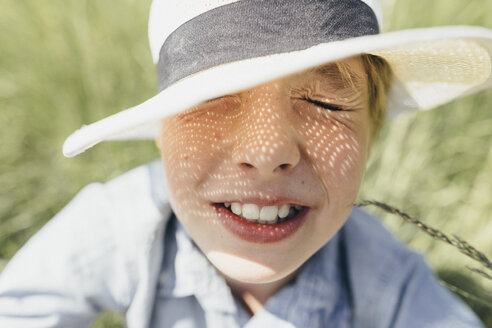 Boy with closed eyes wearing a hat sitting in field - KMKF00341