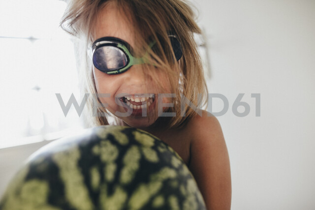 Happy girl with a watermelon wearing swimming goggles - KMKF00344 - Katharina Mikhrin/Westend61