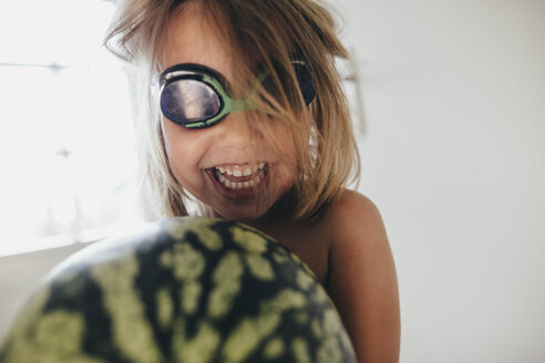 Happy girl with a watermelon wearing swimming goggles - KMKF00344