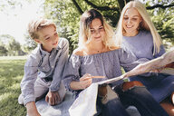 Two young women and a boy looking at map in a park - KMKF00346