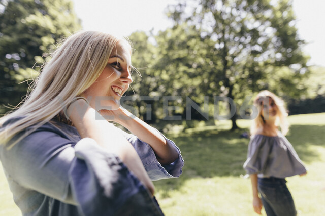 Two happy young women in a park - KMKF00349
