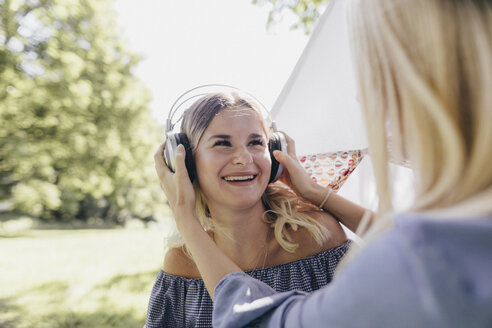 Two happy young women with headphones in a park - KMKF00355