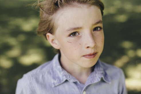 Portrait of serious boy outdoors - KMKF00358