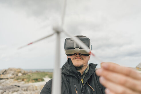 France, Brittany, Meneham, man with miniature wind turbine wearing VR glasses at the coast - GUSF00948