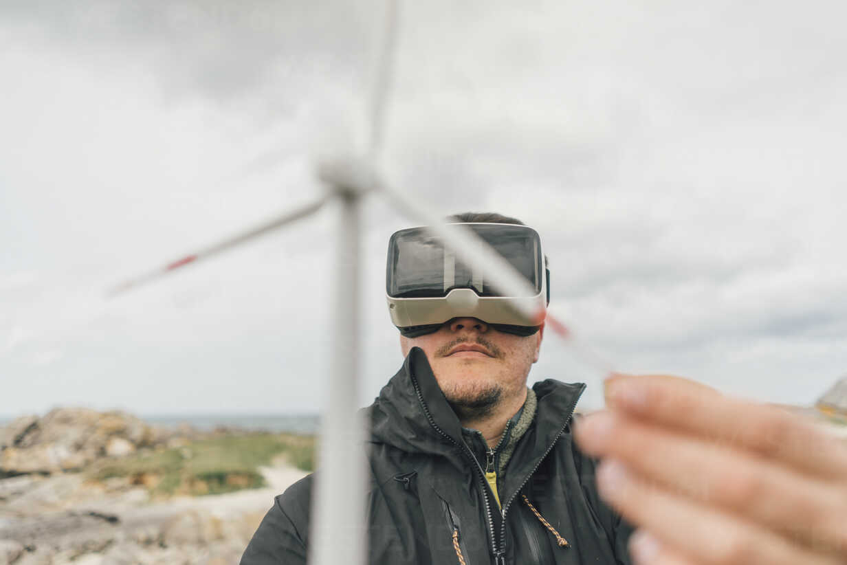France, Brittany, Meneham, man with miniature wind turbine wearing VR glasses at the coast - GUSF00948 - Gustafsson/Westend61