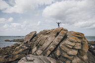 France, Brittany, Meneham, man standing on rock formation at the coast - GUSF00963