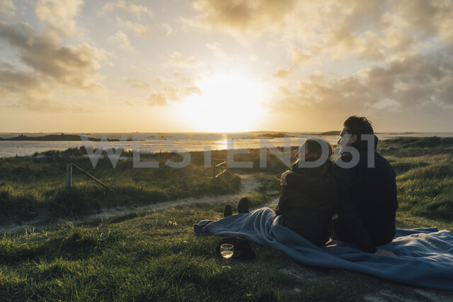 France, Brittany, Landeda, couple sitting  at the coast at sunset - GUSF00969 - Gustafsson/Westend61
