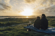 France, Brittany, Landeda, couple sitting  at the coast at sunset - GUSF00969