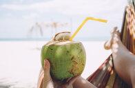 Thailand, Koh Lanta, woman's hand holding fresh coconut - GEMF02051