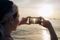 Thailand, Koh Lanta, woman taking photo with cell phone at sunset - GEMF02054