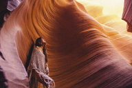 Woman looking up at sunlight in cave, Antelope Canyon, Page, Arizona, USA - ISF08844