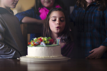 Girl blowing out candles on birthday cake - ISF08880