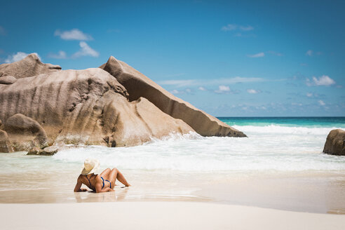 Rear view of mid adult woman in bikini relaxing at beach against blue sky, Seychelles - FSIF03020