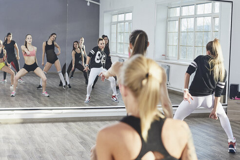 Female dancers reflecting on mirror while dancing in rehearsals at studio - FSIF03029