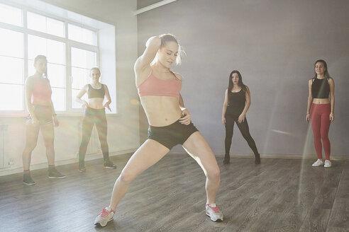 Friends watching at confident female dancing on parquet floor at studio - FSIF03038