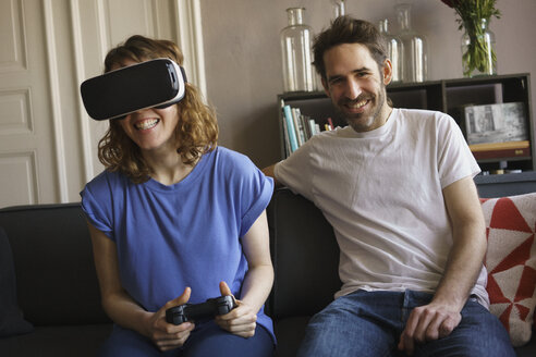 Portrait of smiling man sitting by woman playing on virtual reality headset in living room at home - FSIF03059