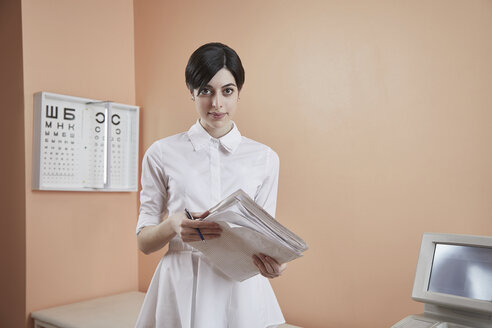 Portrait of nurse holding papers while standing in hospital - FSIF03077