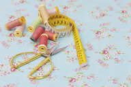 Close-up of various spools and scissors with tape measure on blue fabric - FSIF03104