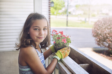 Girl planting flowers in planter box, looking at camera smiling - ISF08901