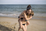 Women playing piggyback on beach, Amagansett, New York, USA - ISF08955