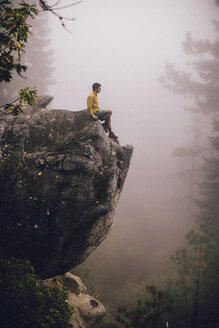 Young man sitting on rock, looking at view, near Shaver Lake, California, USA - ISF08991