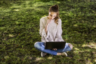 Pensive woman sitting on a meadow using laptop - FMKF05089