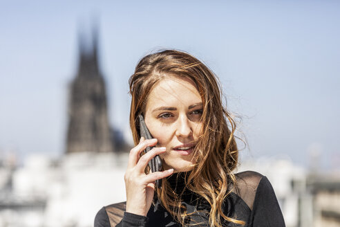 Germany, Cologne, portrait of woman on the phone - FMKF05095