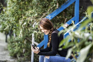 Smiling woman sitting on stairs looking at smartphone - FMKF05098