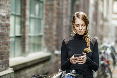 Portrait of woman with bicycle looking at cell phone - FMKF05104