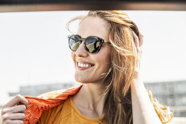 Portrait of smiling woman wearing sunglasses - FMKF05110