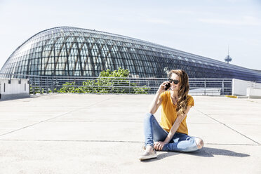 Germany, Cologne, smiling woman on the phone sitting on parking level - FMKF05113