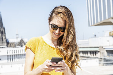 Germany, Cologne, smiling woman using smartphone outdoors - FMKF05116