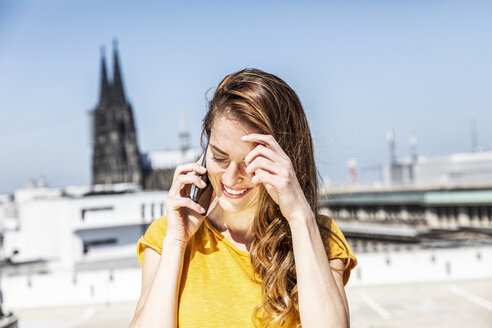 Germany, Cologne, smiling woman on the phone - FMKF05119