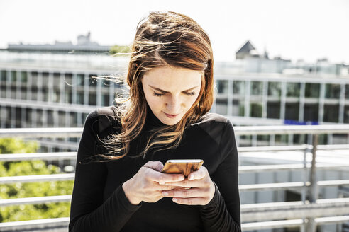 Woman text messaging on roof terrace - FMKF05122
